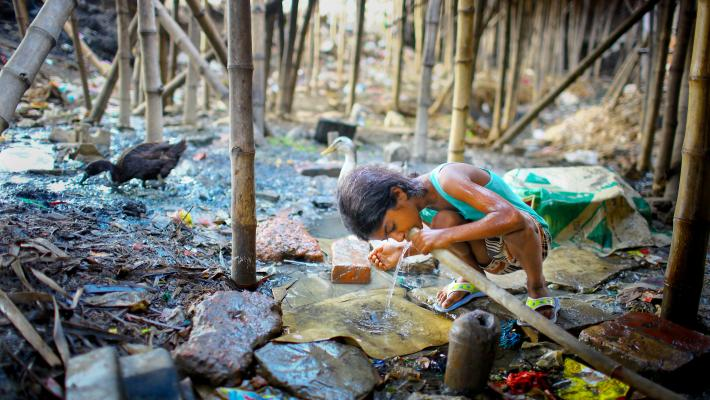 Image of child drinking water from pipe near garbage